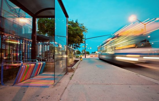 bus stop with passing cars and busses